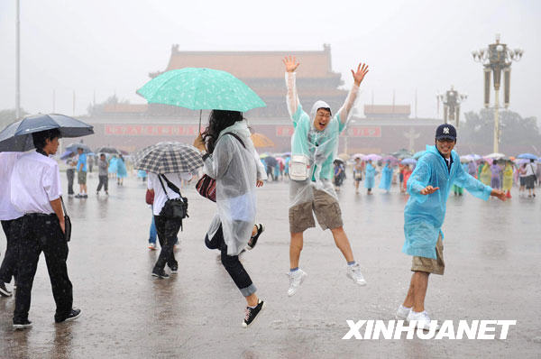 7月17日,几名来自韩国的游客在雨中的天安门广场嬉戏。