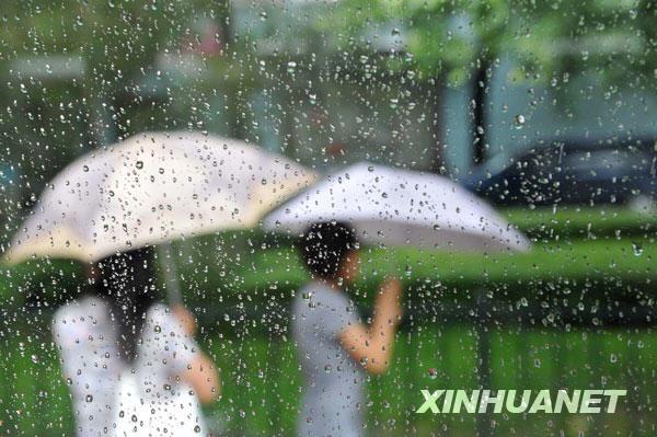 7月17日,游客走在雨中的北京街头。