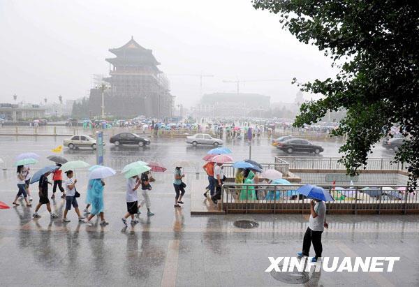 7月17日,游客冒雨在天安门广场游览。