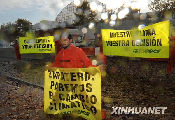 """11月5日,在西班牙巴塞罗那举行的2009年联合国第五次气候变化谈判的会场外,绿色和平组织成员模拟""""风雨交加""""的恶劣天气效果,揭示气候变化给人类生存环境带来的灾难性破坏,呼吁发达国家为解决气候变化问题迅速采取实际行动。当日,2009年联合国第五次气候变化谈判在巴塞罗那继续进行。"""
