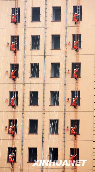 11月9日,消防队员进行高楼挂钩梯连挂表演。